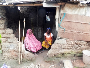 Mother and Grandmother of an Anansi applicant sitting inside their home.